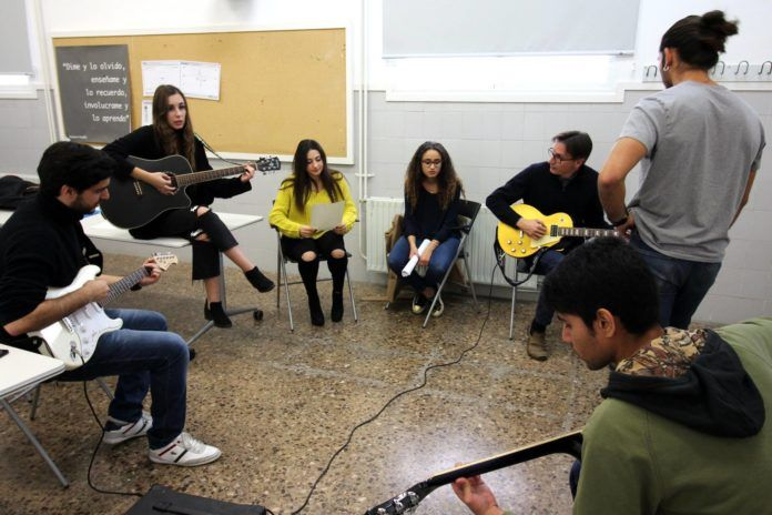 ESET students and teachers learning to play the guitar.