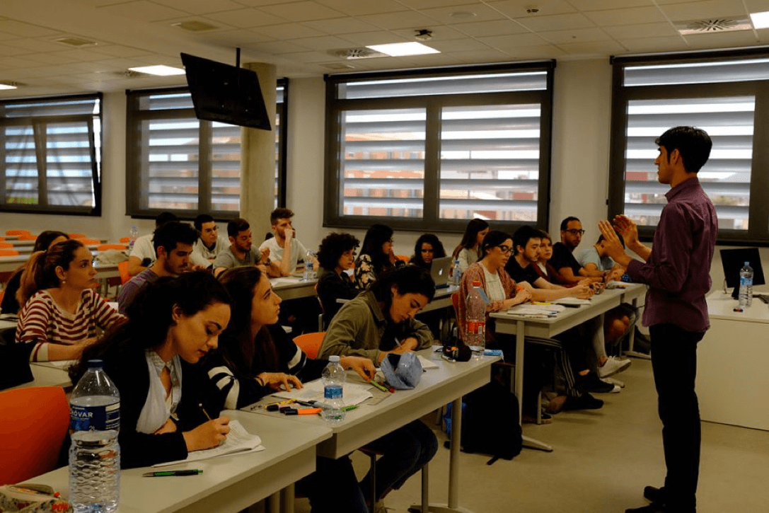 A coordinator gives a talk in front of a large class.
