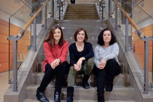 Tres de los miembros del equipo del Servicio de Carreras Profesionales de la CEU UCH que asesoran a los estudiantes sobre las prácticas, posan sonrientes en las escaleras del campus