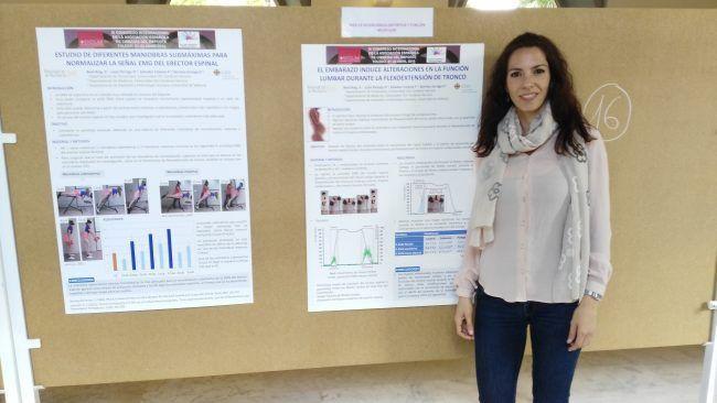 La Doctora Biviá ante dos de los pósters presentados, tras su exposición.