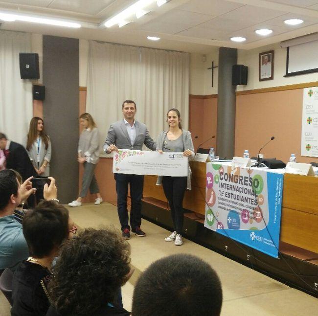 Alba García recibe el premio a la mejor comunicación en Fisioterapia de manos del vicedecano del ICOFCV