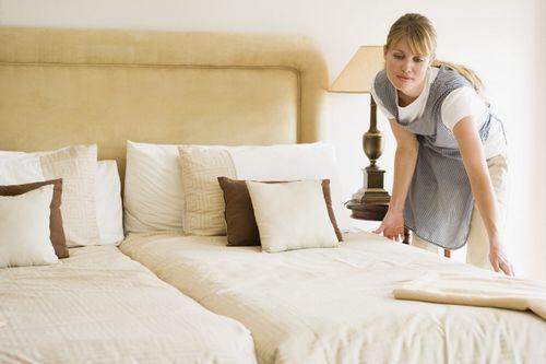 Una camarera de piso realizando su trabajo en una postura poco ergonómica