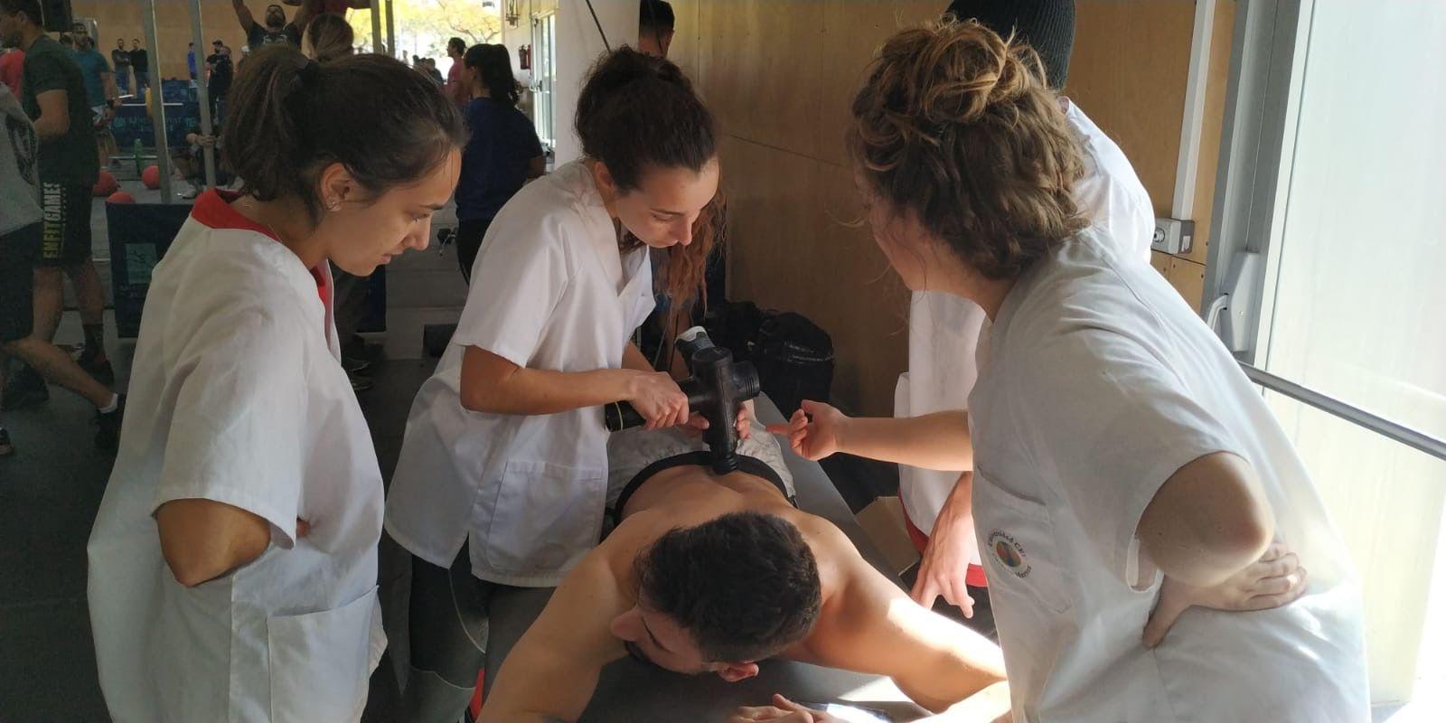 Dando la batalla por el deporte. Estudiantes de Fisioterapia CEU-UCH en la batalla del crossfit de Castellón. En la imagen utilizando una pistola de masaje. 2020.
