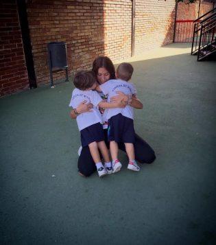 Imagen. Maestra en práctica abrazando a sus alumnos