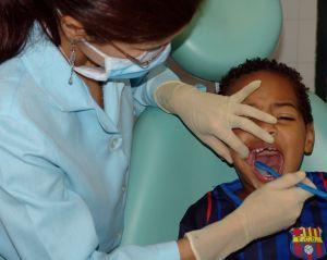 Fotografia de una dentista que esta enseñando a cepillar los dientes a un niño