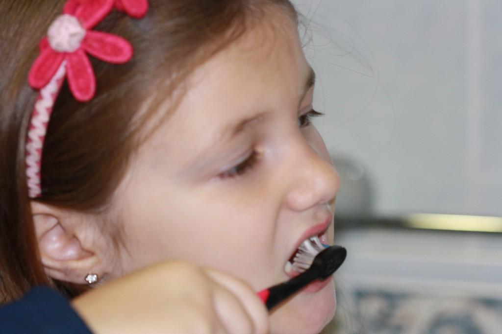 Niña de perfil cepillando los dientes