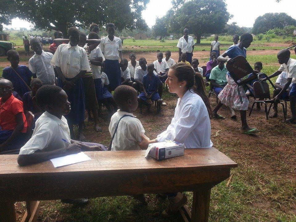 Alumna con niños haciendo revisiones