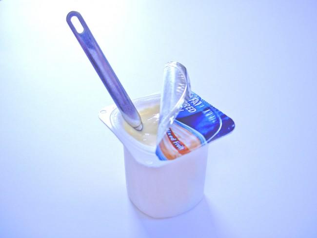 fotografia se una tarrina de yogurtcon una cuchara