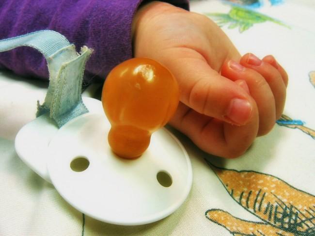 Foto de un chupete y mano de un niño durmiendo
