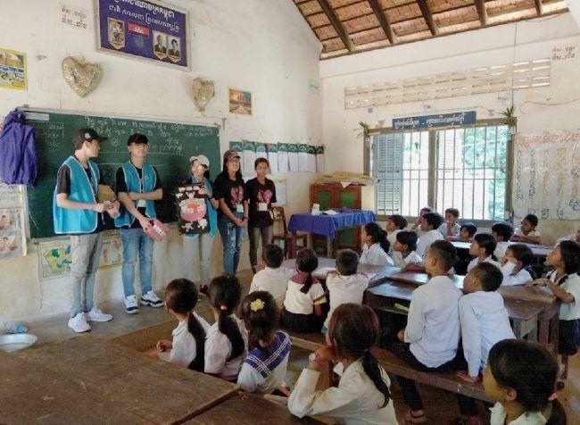 Voluntarios de la misión dental en Camboya formando a un grupo de niños en un aula