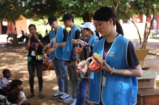 Voluntarios de la misión solidaria en camboya enseñando a un grupo de niños a cepillarse los dientes