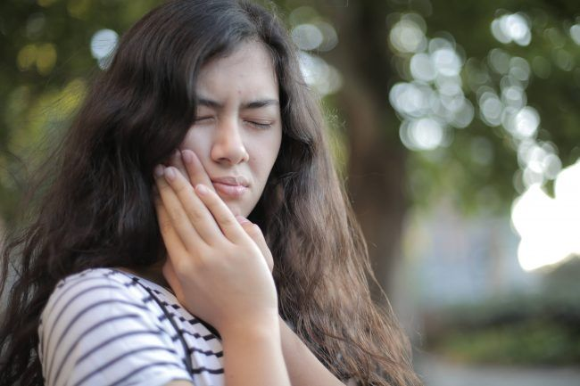 Chica con dolor de boca por las muelas del juicio