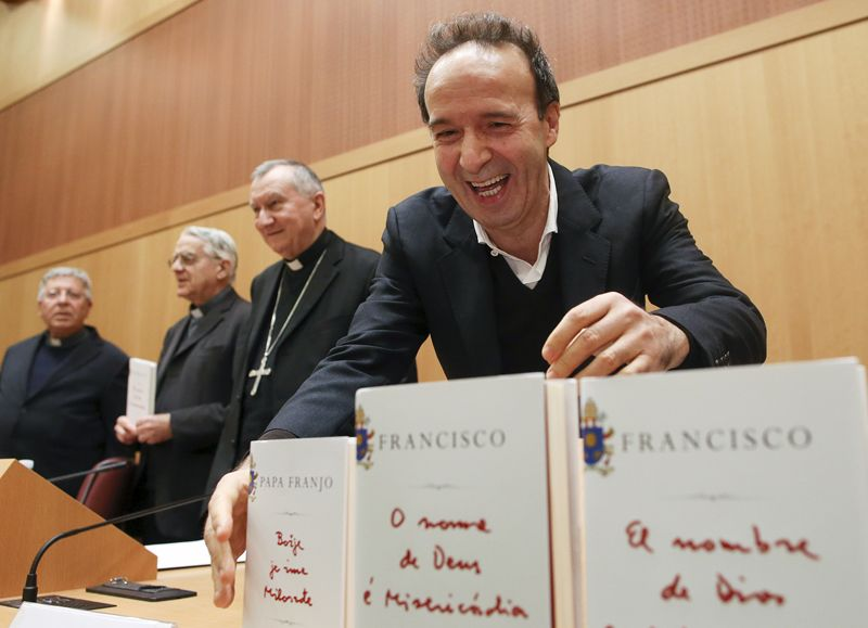 "Italian actor Roberto Benigni, far right, takes a copy of Pope Francis' book ""The Name of God is Mercy"" as he arrives during a news conference for the launch of the book at the Vatican on January 12, 2016. Photo courtesy of REUTERS/Alessandro Bianchi *Editors: This photo may only be republished with RNS-POPE-BENIGNI, originally transmitted on Jan. 12, 2016."
