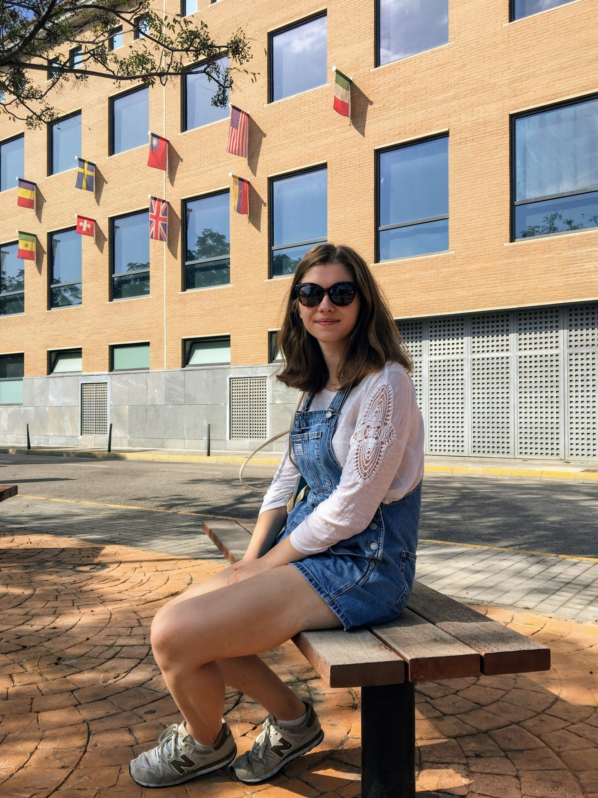 A photo of a girl sitting in front of the Faculty of Law, Business and Political Science
