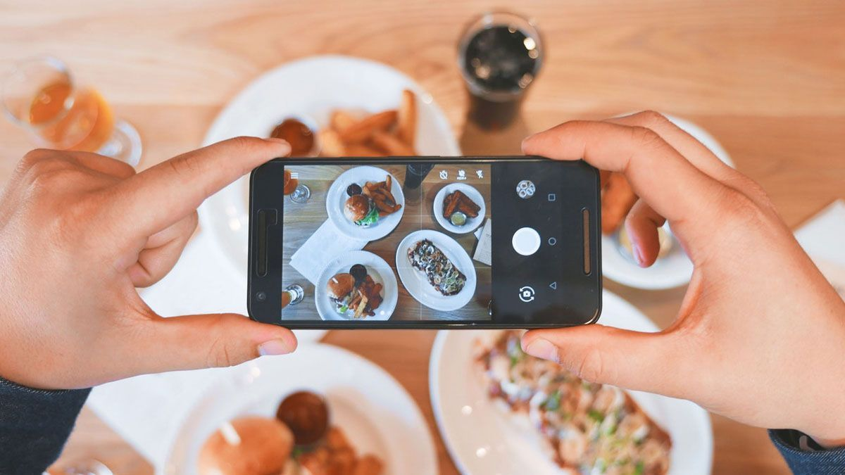 person taking picture of meals with smartphone