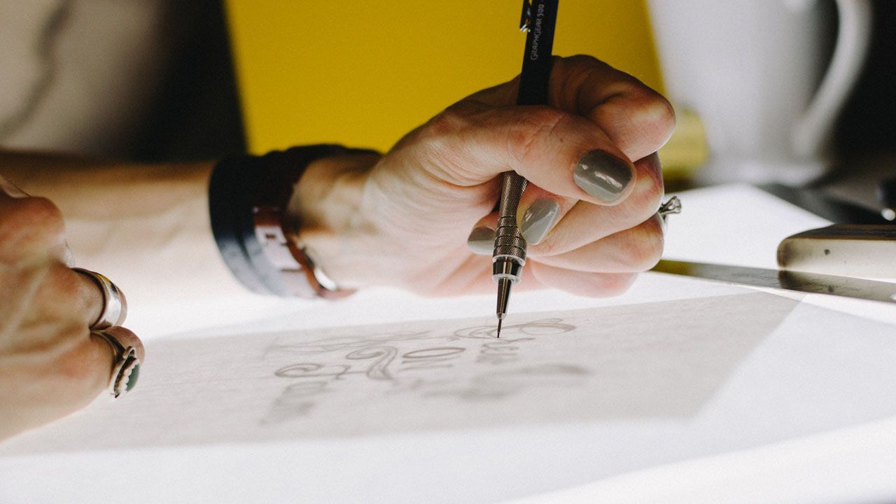 person sketching on tracing paper